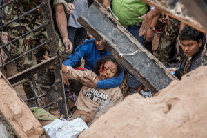 KATHMANDU, NEPAL - APRIL 25: (EDITORS NOTE: Image contains graphic content.) Emergency rescue workers find a survivor in the debris of Dharara tower after it collapsed on April 25, 2015 in Kathmandu, Nepal. More than 100 people have died as tremors hit Nepal after an earthquake measuring 7.9 on the Richter scale caused buildings to collapse and avalanches to be triggered in the Himalayas. Authorities have warned that the death toll is likely to be much higher. (Photo by Omar Havana/Getty Images)